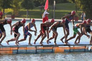 Tyler Smith ( centre in red and blue trisuit - red cap) enters the water yesterday - click on picture to enlarge